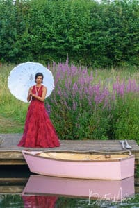 Indian bride standing under an umbrella next to a pond with a boat
